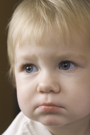 glum: Blonde 14 month old with downcast expression