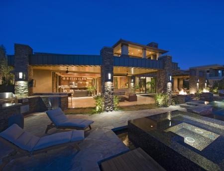 iluminados: Exterior de la casa iluminada por la noche con muebles de jardín