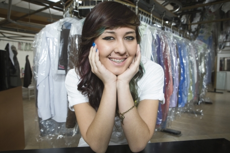 elbow brace: Young smiling woman working in laundrette
