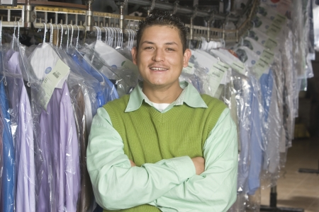 Man working in the laundrette  standing infront of clothes rail Stock Photo - 20741980