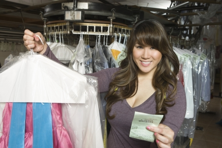 laundrette: Woman working in the laundrette holding a receipt and clothes