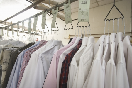 Clothes hanging in the laundrette Standard-Bild