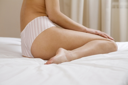 knickers: Mid adult sits half dressed on a bed