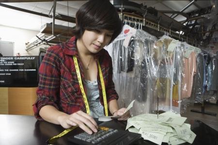 Vrouw berekening van de ontvangsten in de wasserette Stockfoto