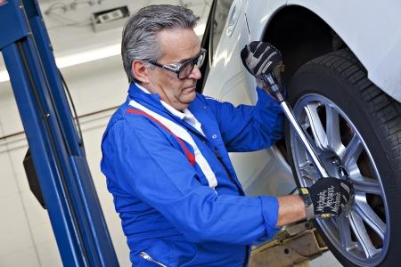 mot: Car mechanic working on car tire LANG_EVOIMAGES