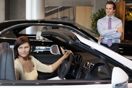 test drive: Woman having a test drive while salesperson standing besides car