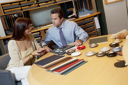decisionmaking: Salesperson showing color samples to female client LANG_EVOIMAGES