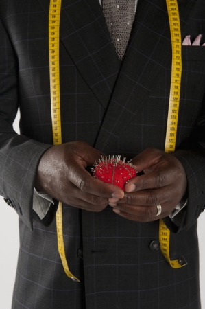 pers: Mid section of man wearing suit holding pincushion