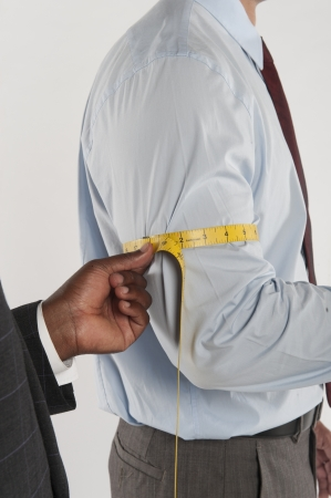 customer tailor: Tailor taking the measurement of a customer