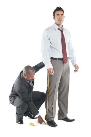 customer tailor: Tailor taking measure leg of customer LANG_EVOIMAGES