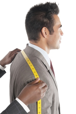 customer tailor: Tailor measuring across upper back from shoulder to shoulder of customer LANG_EVOIMAGES