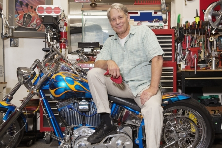 occ: Senior man sitting on motorcycle in workshop LANG_EVOIMAGES