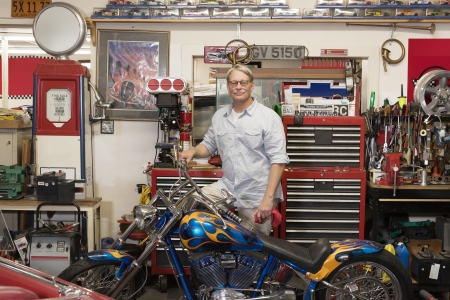 occ: Senior man standing behind motorcycle in automobile repair shop LANG_EVOIMAGES