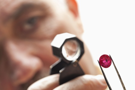 jeweler: Close up of gemstone with jeweler looking through magnifying glass LANG_EVOIMAGES