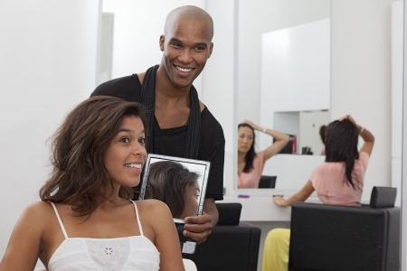 hairdresser: Hairdresser holding a mirror behind young woman