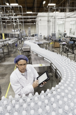 factory worker: High angle view of man examining bottles at bottling plant