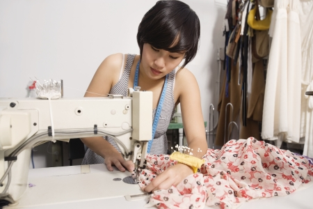occ: Fashion designer sewing fabric LANG_EVOIMAGES