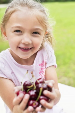 bing: Portrait of a happy girl with hands full on bing cherries