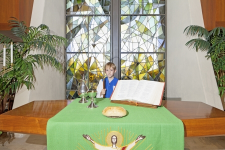 christian community: Little boy standing by the altar table