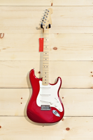 fender stratocaster: Fender Stratocaster red and white guitar on wood grain wall