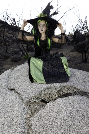 sitt: Little young girl costumed as witch sitting on rock looking away