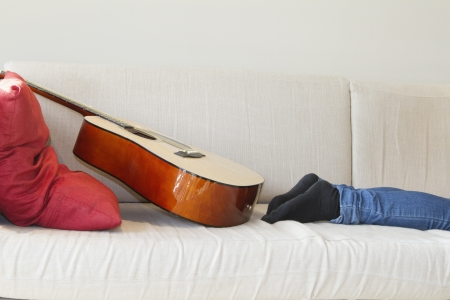 low section: Low section of mans leg with guitar kept on sofa