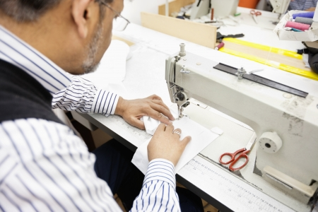 mach 1: Close-up of man sewing with machine LANG_EVOIMAGES