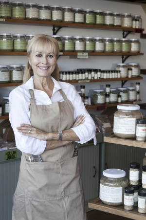 decisionmaking: Portrait of a happy senior woman with arms crossed in spice store LANG_EVOIMAGES