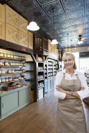 negocios comida: Retrato de un feliz altos mercader de especias femenino de pie con los brazos cruzados en la tienda LANG_EVOIMAGES