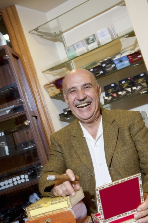 gro: Portrait of cheerful mature man smoking cigar in tobacco store
