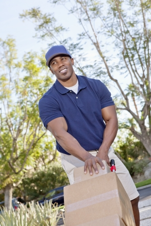 handtruck: Happy young African American male pushing handtruck
