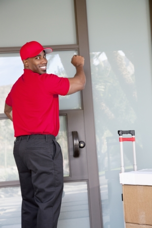 oc: Young delivery man with packages looking back while knocking on door
