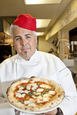 pokrývka hlavy: Portrait of a confident chef wearing headgear while holding pizza in commercial kitchen