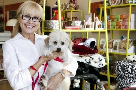 pet shop: Portrait of a happy senior woman carrying dog in pet shop