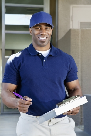 20s adult: Portrait of a happy young African American delivery man with clipboard
