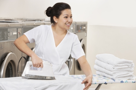 laundromat: Happy young employee ironing clothes while looking away in Laundromat