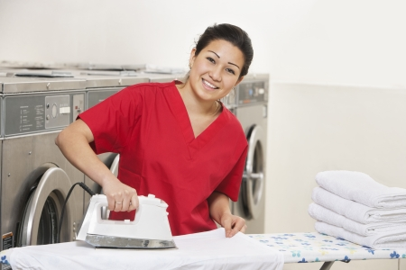 laundromat: Portrait of a cheerful young employee ironing in Laundromat LANG_EVOIMAGES