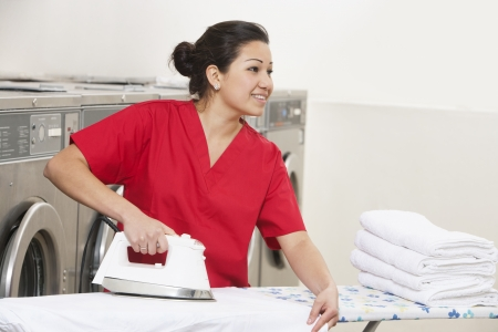 laundromat: Happy young female employee ironing while looking away in Laundromat