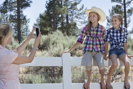 femal: Mother photographing daughters through cell phone as they sit on fence at park