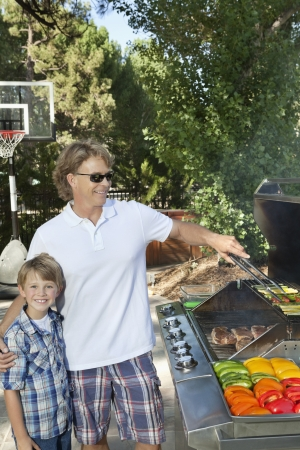 barbecuing: Portrait of a little boy with father barbecuing vegetable on barbecue grill in lawn LANG_EVOIMAGES
