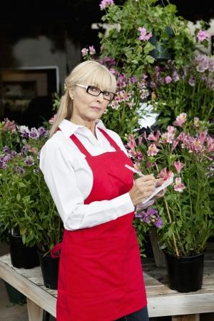 garden center: Portrait of a senior florist making notes in garden center