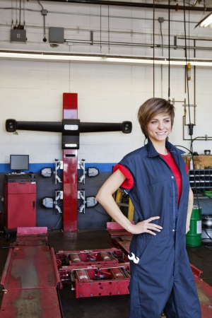 automobile repair shop: Happy young female mechanic with hands on hips in automobile repair shop