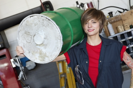 Portrait of a happy young female mechanic carrying oil drum on shoulder in car workshop Stock Photo - 20743465