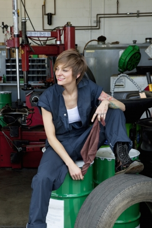 automobile repair shop: Happy young female mechanic sitting on oil drum in automobile repair shop