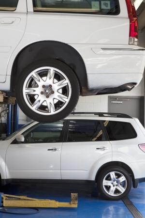 car hoist: Car on hoist in automobile repair shop