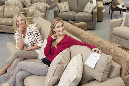 furniture store: Portrait of happy mother and daughter sitting on sofa in furniture store LANG_EVOIMAGES