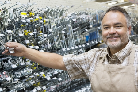 hardware: Portrait of a happy mature salesperson holding metallic equipment in hardware store