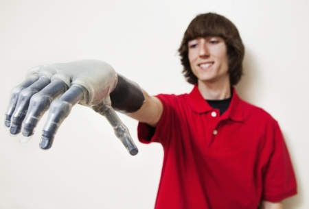health facility: Young man looking at his prosthetic hand over gray background