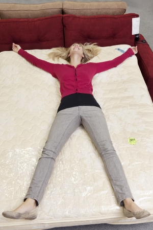 decisionmaking: High angle view of woman lying on mattress in furniture store LANG_EVOIMAGES