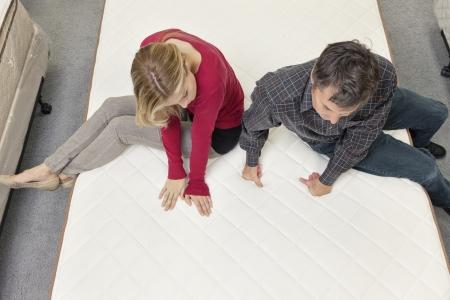 furniture store: Friends sitting on mattress in furniture store